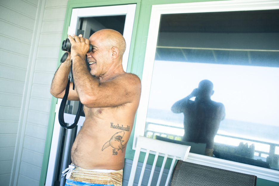 Michael Ho anxiously watches Mason Ho's Pipe Masters trial heat from the porch of a nearby Pipe patio.